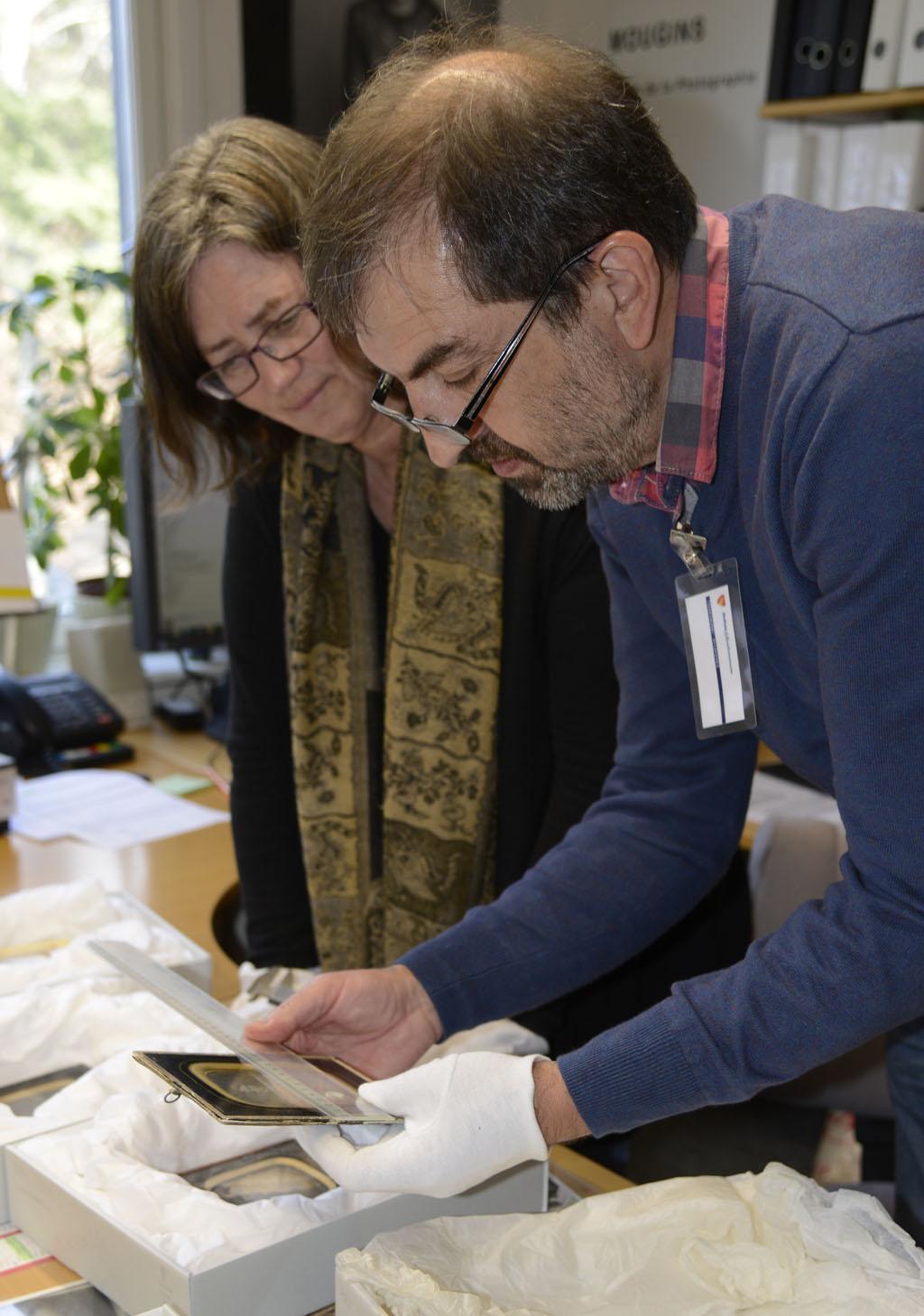 Fotokonservator Wlodek Witek demonstrerer arbeidet for leder av billedarkivet, Kari Grindland. Foto: Roderick Ewart / Østfold fylkes billedarkiv.